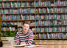 Smiling male student with open book working in a library.  Stock Photos