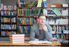 Smiling male student with open book working in a library Royalty Free Stock Photos