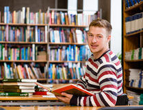 Smiling male student with open book working in a library and looking at camera.  Stock Photography