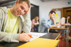 Smiling male student with others writing notes in classroom Stock Photos