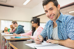 Smiling male student with others writing notes in classroom Royalty Free Stock Photos