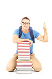 Smiling male student on a pile of books giving thumb up. Smiling male student with school bag on a pile of books giving thumb up isolated on white background Stock Photos