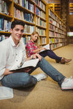 Smiling male student revising on floor. In library Royalty Free Stock Photography