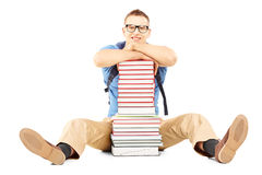 Smiling male student with school bag on a pile of books. Isolated on white background Stock Photography