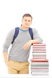 Smiling male student with school bag posing on a pile of books. Isolated on white background Stock Photo
