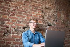 Cheerful hipster man skilled freelancer working on laptop computer in modern interior. royalty free stock images