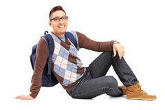 Smiling male student sitting on the floor Royalty Free Stock Photo