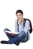 Smiling male student sitting on floor with book Stock Photography