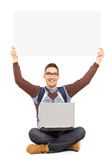 Smiling male student sitting with laptop and holding a panel. Smiling male student sitting with laptop and holding a blank panel, isolated on white background Royalty Free Stock Images
