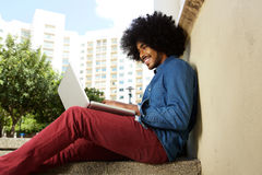 Smiling male student sitting outside working on laptop Stock Photos