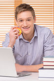 Smiling male student with stack of books. Young man holding apple and using computer Stock Image