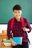 Smiling male student standing in  classroom. Smiling asian male student standing in  classroom Royalty Free Stock Image