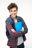 Smiling male student standing with folders. Over gray background Royalty Free Stock Photo