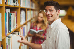 Smiling male student taking book Stock Images