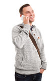 Smiling male student talking on the phone. A portrait of a smiling male student, talking on a phone, isolated on white background Stock Photography