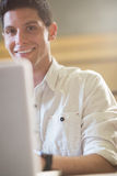 Smiling male student using laptop. In lecture hall Royalty Free Stock Photography