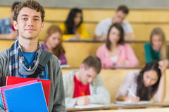 Smiling male with students sitting at lecture hall Stock Photos