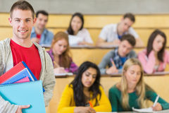 Smiling male with students sitting at lecture hall Royalty Free Stock Photography