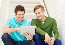 Smiling male students with tablet pc computer. Education and technology concept - smiling male students with tablet pc computer sitting on staircase Royalty Free Stock Photo