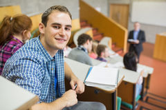 Smiling male with students and teacher at lecture hall. Portrait of a smiling male with students and teacher at the college lecture hall Stock Photos