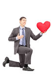 A smiling male in a suit kneeling with red heart Stock Photography