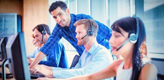Male supervisor assisting telemarketer at call center. Smiling male supervisor assisting telemarketer at desk in call center royalty free stock photos