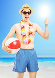 Smiling male in swimming shorts, holding a ball and giving thumb up. Smiling male in swimming shorts, holding a beach ball and giving thumb up, on a beach next Royalty Free Stock Photography