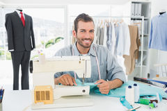 Smiling male tailor sewing in workshop Royalty Free Stock Photos