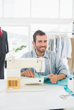 Smiling male tailor sewing in workshop Stock Photo