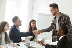 Team leader handshaking new member to diverse work group. Smiling male team leader shaking hand of new team member at company meeting in boardroom, partners Stock Photos