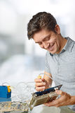 Smiling male tech cleans faulty computer processor. In hardware repair workshop stock image