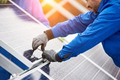 Smiling male technician in blue suit installing photovoltaic blue solar modules with screw. Man electrician panel sun sustainable resources renewable energy stock image