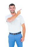 Smiling male technician pointing at copy space on white background Stock Photography