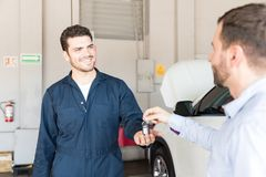 Smiling Technician Receiving Car Key From Customer At Repair Sho. Smiling male technician receiving car key from customer for service at auto repair shop Royalty Free Stock Image