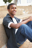 Smiling Male Teenage Student Sitting Outside Stock Photo