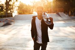 Smiling male teenager guy holding skateboard. On shoulders and looking at camera outdoors Stock Photo