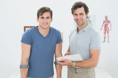 Smiling male therapist and disabled patient with reports. Portrait of a smiling male therapist and disabled patient with reports in the medical office Royalty Free Stock Photos