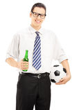 Smiling male with tie holding a beer bottle and ball. Smiling male with tie holding a beer bottle and soccer ball isolated on white background Stock Images