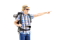 Smiling male tourist with backpack pointing with his finger. Isolated on white background Stock Photo