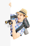 Smiling male tourist looking through binocular behind a panel. Isolated on white background Royalty Free Stock Photos