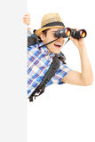 Smiling male tourist loooking through binocular behind a panel. Smiling male tourist loooking through binocular behind a blank panel isolated on white background Royalty Free Stock Photography