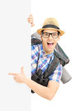 Smiling male tourist pointing on a blank panel Stock Image