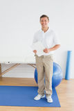 Smiling male trainer with clipboard in gym at hospital. Full length portrait of a smiling male trainer with clipboard in the gym at hospital Royalty Free Stock Images