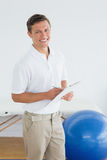 Smiling male trainer with clipboard in gym at hospital. Portrait of a smiling male trainer with clipboard in the gym at hospital Royalty Free Stock Photo