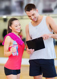 Smiling male trainer with woman in the gym. Fitness, sport, training, gym and lifestyle concept - smiling male trainer with clipboard and women with water bottle Royalty Free Stock Images