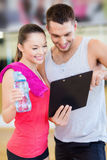 Smiling male trainer with woman in the gym. Fitness, sport, training, gym and lifestyle concept - smiling male trainer with clipboard and women with water bottle Stock Photography