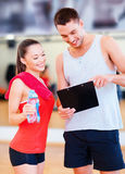 Smiling male trainer with woman in the gym. Fitness, sport, training, gym and lifestyle concept - smiling male trainer with clipboard and women with water bottle Stock Photos