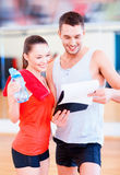 Smiling male trainer with woman in the gym. Fitness, sport, training, gym and lifestyle concept - smiling male trainer with clipboard and women with water bottle Royalty Free Stock Photography