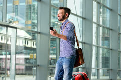 Smiling male traveler walking with bag and cell phone. Side portrait of smiling male traveler walking with bag and cell phone Royalty Free Stock Images