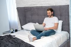 Smiling male using laptop in bedroom. With modern interior Stock Photos